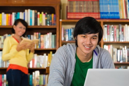 adult indonesia: Student - Young Asian man in library with laptop learning, a female student standing in the Background on a shelf reading book Stock Photo