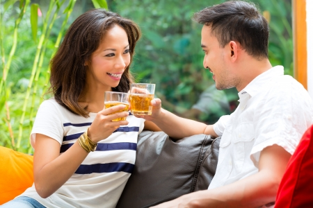 Young Indonesian couple - man and woman - at home, drinking together and clinking glasses photo