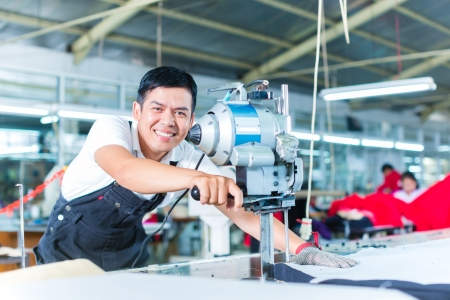 garment industry: Indonesian worker using a cutter - a large machine for cutting fabrics - in a asian textile factory, he wears a chain glove