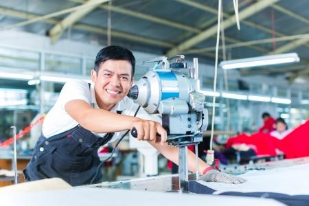 indonesisch: Indonesische werknemer met een mes - een grote machine voor het snijden van stoffen - in een Aziatisch textielfabriek, draagt hij een ketting handschoen