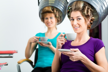 chitchat: women at the hairdresser drinking coffee or cappuccino and chit-chat, while your hair drying under a hairdryer