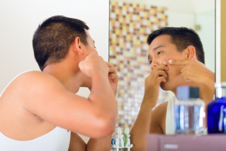 Asian man discovering a pimple in face photo