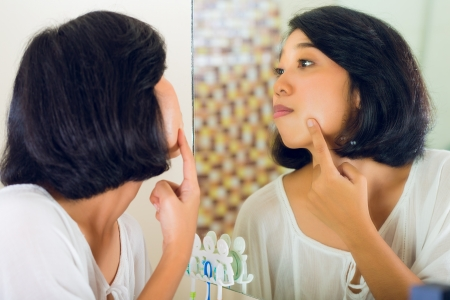 Asian woman discovering a pimple in face photo