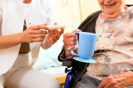 ministration: Young nurse and female senior in nursing home, the old lady sitting in a wheel chair Stock Photo
