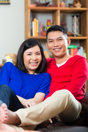 intimately: Young Indonesian couple - man and woman - sitting at home on a couch, its weekend and they enjoying the leisure time
