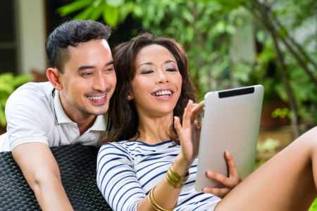 Young Indonesian couple - man and woman - sitting with a tablet computer in the garden photo