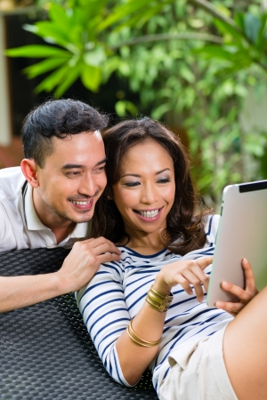 Young Indonesian couple - man and woman - sitting with a tablet computer in the garden Stock Photo - 24283965