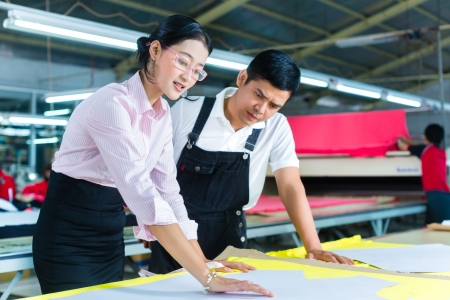 indonesian people: Indonesian Worker or foreman and dressmaker, tailor or designer looking at pattern on a table in a Asian textile factory