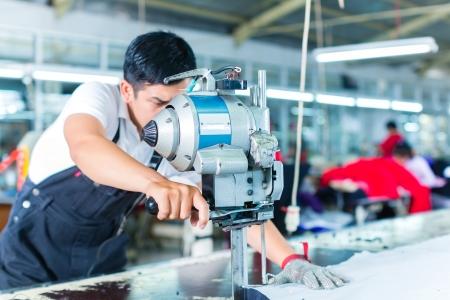 Indonesische werknemer met een mes - een grote machine voor het snijden van stoffen - in een Aziatisch textielfabriek, draagt hij een ketting handschoen