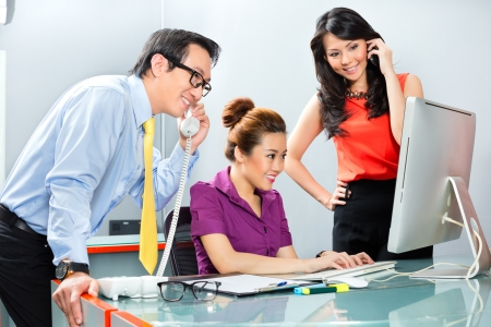 Asian business workers in an office working together as a team for success in a joint project photo