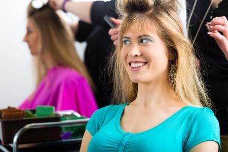 Hairdresser - hair stylist curling hairs, a female customer gets a haircut photo