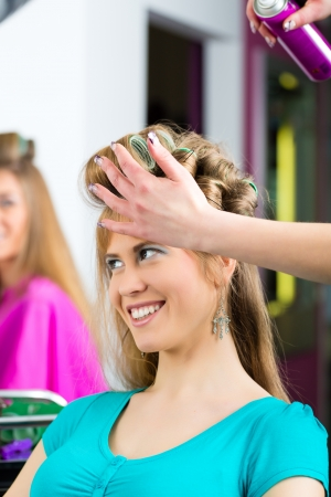 Women at the hairdresser being curled photo