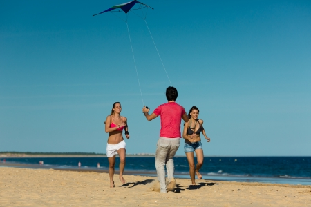 Group of young people playing with a kite on beach in sand outdoors in summer photo