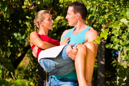 carries: Winegrower man carries a woman on his arms at the  vineyard smiling