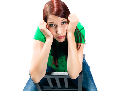 clueless: Woman is sitting on a Chair in the Studio and is demotivated or frustrated, even clueless or bored