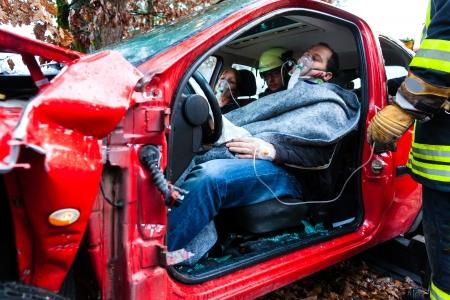 paramedic: víctima en un vehículo accidentado, recibe los primeros auxilios de los bomberos Foto de archivo