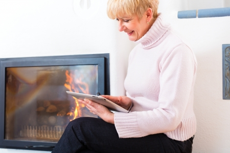 warm home: Older Woman or female Pensioner sitting at home in front of the furnace, writing emails on the tablet computer or reading a e-book Stock Photo