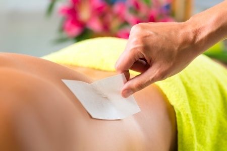 sugared: Man in Spa getting back waxed or sugared for hair removal Stock Photo