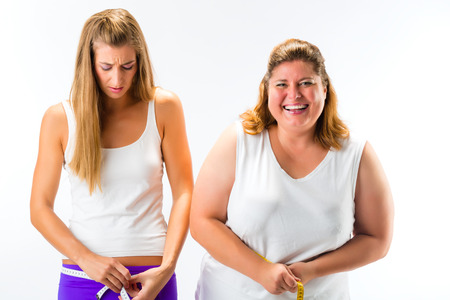 envious: Thin and fat woman measuring waist with measuring tape, one woman looking unhappy or envious Stock Photo