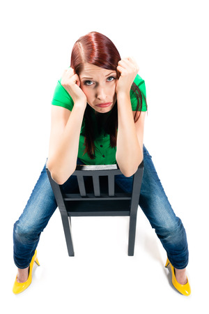 demotivated: Woman is sitting on a Chair in the Studio and is demotivated or frustrated, even clueless or bored