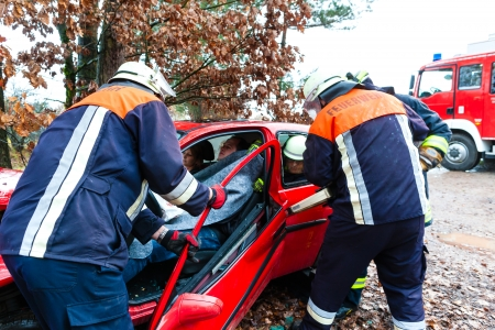 brigade: Fire brigade rescues accident Victim of a car using a hydraulic rescue tool Stock Photo