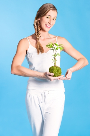 symbolically: Young woman holding symbolically a small tree