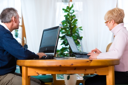 communicative: two elderly people sitting at home on the table and writing emails on the computer and laptop