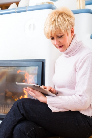 communicative: Older Woman or female Pensioner sitting at home in front of the furnace, writing emails on the tablet computer or reading a e-book Stock Photo