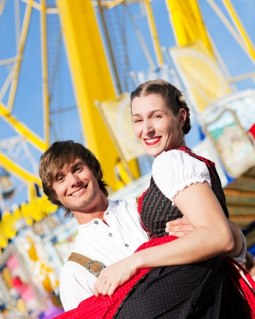 tracht: Couple in Tracht flirting at big wheel