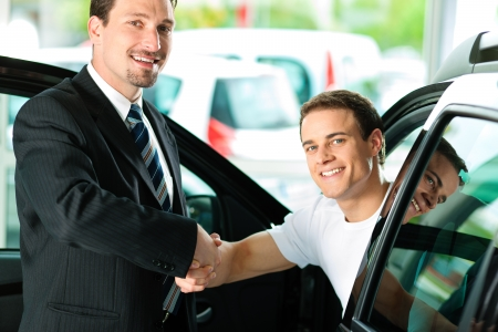 Man buying a car in dealership sitting in his new auto; they are shaking hands to close the deal photo