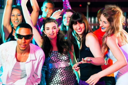 dancefloor: Dance action in a disco club - group of people, men and women of different ethnicity, dancing to the music having lots of fun