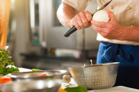 Close up of chef in a commercial restaurant or hotel kitchen working, he is preparing an onion and vegetables photo