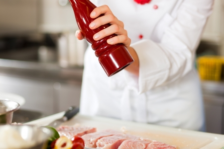 Close up of a chef or cook in a commercial restaurant or hotel kitchen working, peppering a dish photo