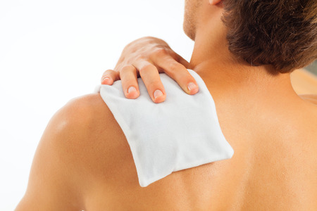 warming therapy: Young man with coolpack on his shoulder has a tension