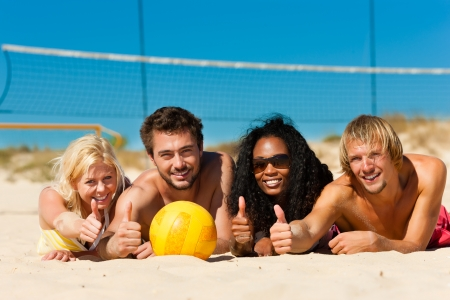 beach volleyball: Group of friends - women and men - playing beach volleyball, they having a break and lying in the sun