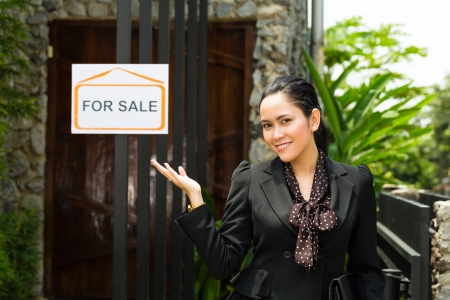 accommodation broker: Real estate - Young Indonesian real estate showing an house or apartment, it could be the landlord too