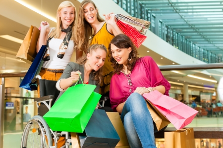 Four female friends with shopping bags having fun while shopping in a mall, stores , one woman is sitting in a wheelchair photo
