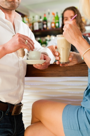 Attractive couple in cafe or coffeeshop, the barista to be seen photo