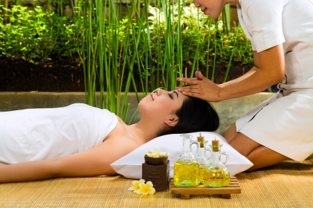Beautiful Asian woman having a wellness Head massage in a tropical setting and feeling visibly good about it photo