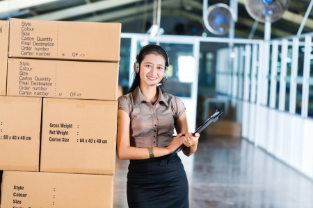 shipment: Young Asian woman in a suit with headset in a Indonesian logistics warehouse, she is from the Customer Service