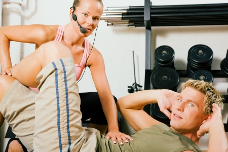 Young man practicing sit-ups in a gym under supervision by his personal trainer photo