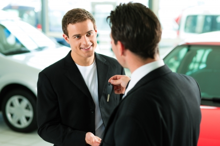 car dealer: Man at a car dealership buying an auto, the sales rep giving him the key