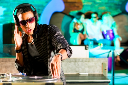 Black DJ in a club at the turntable photo