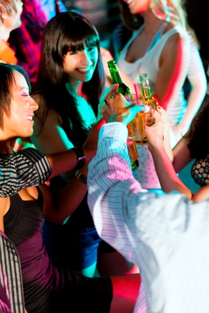 Dance action in a disco club - group of people, men and women of different ethnicity, dancing to the music having lots of fun Stock Photo - 24433025