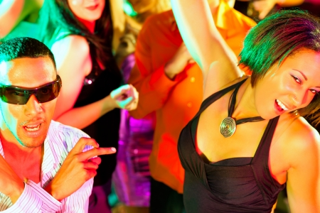 flirting: Dance action in a disco club - group of people, men and women of different ethnicity, dancing to the music having lots of fun