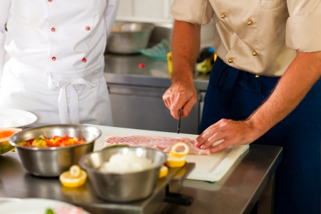 Close up of chefs in a commercial restaurant or hotel kitchen working, they are preparing an fish fillet and vegetables photo