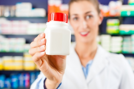 Female pharmacist is standing in her drugstore behind the counter holding a medicine bottle photo