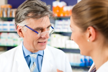 pharmacy store: Two pharmacists with prescription in hand consulting each other in a pharmacy