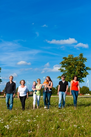 extended family: Family and multi-generation - mother, father, children and grandmother having fun on meadow in summer