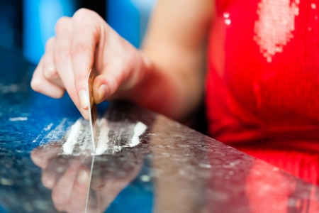 drug abuse: Young woman snorting cocaine with her credit card, close-up